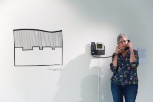 White wall with black and white graphic and woman talking on a wall-mounted phone.